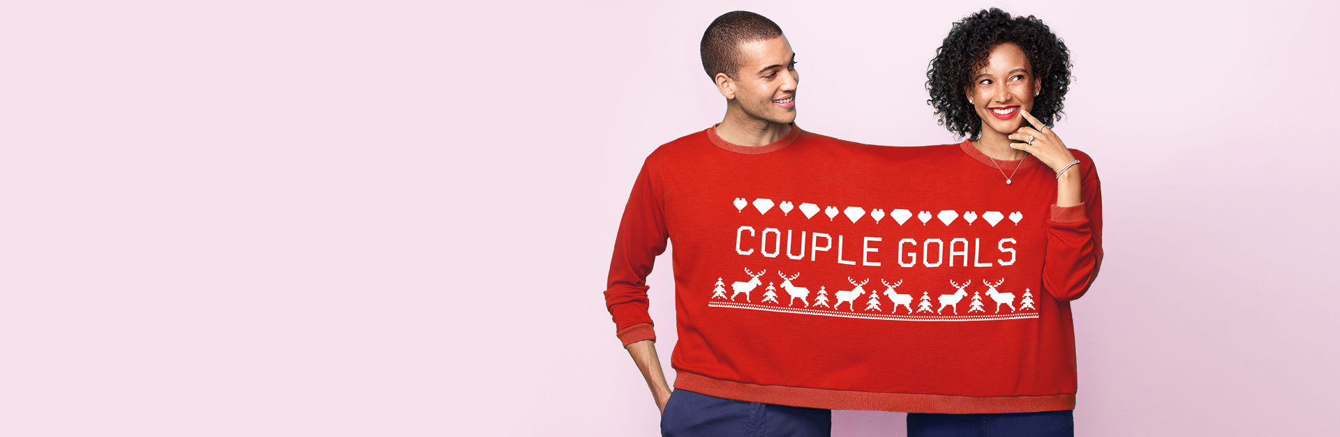 """A couple sharing an over-sized Christmas sweater. The sweater reads """"Couple goals""""."""