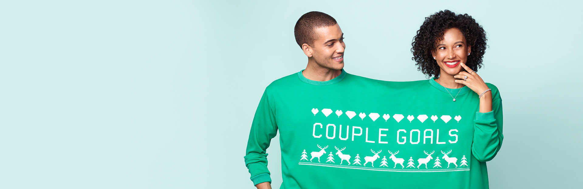 Couple wearing 1 oversized sweater that says 'Couple goals'.