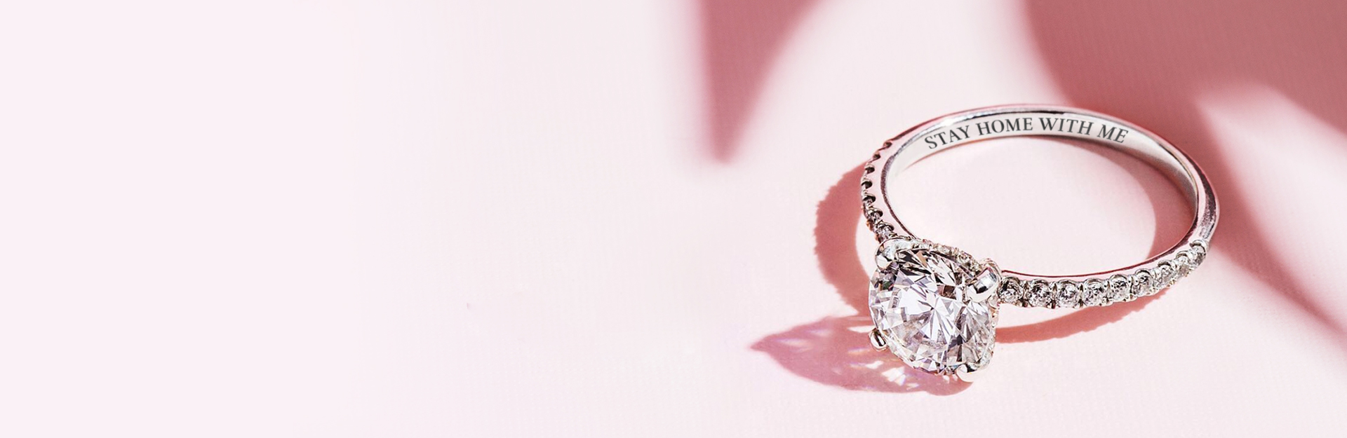 """Image of an engagement ring with an engraving that says """"Stay Home With Me"""""""